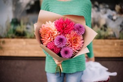 Very nice young woman holding big and beautiful bouquet of fresh different Dahlia flowers in pink, purple, peach and red colors, cropped photo, bouquet close up