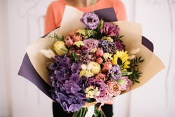 Very nice young woman holding big and beautiful bouquet of fresh hydrangea, sunflower, eustoma, roses, carnations in yellow and deep purple colors, cropped photo, bouquet close up