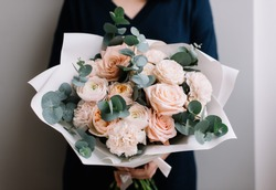 Very nice young woman holding big and beautiful bouquet of fresh roses, carnations, eucalyptus flowers in pastel pink colors, cropped photo, bouquet close up