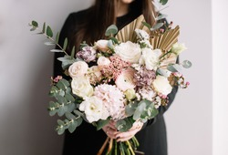 Very nice young woman holding big and beautiful bouquet of fresh roses, carnations, eucalyptus, ranunculus, eustoma, chamellacium, hyacinths flowers in pastel cream and pink colors, bouquet close up