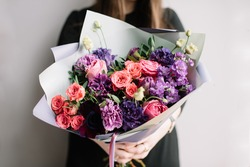 Very nice young woman holding big and beautiful bouquet of fresh roses, carnations, matthiola, eustoma flowers in purple and pink colors, cropped photo, bouquet close up