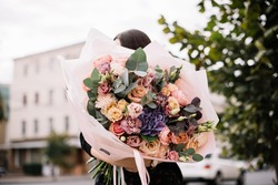 Very nice young woman holding big and beautiful bouquet of fresh roses, eustoma, eucalyptus, carnations hydrangea flowers in cream and purple colors, cropped photo, bouquet close up