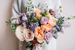 Very nice young woman holding big and beautiful colourful flower wedding bouquet with purple carnations and mattiolas, cream David Austin roses, ranunculus and pistachios