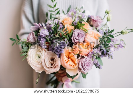 Very nice young woman holding big and beautiful colourful flower wedding bouquet with purple carnations and mattiolas, cream David Austin roses, ranunculus and pistachios #1021598875