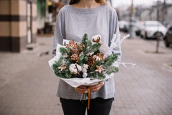Very nice young woman holding big and beautiful winter festive composition of fresh Nobilis spruce, pine cones, cotton, ruskus, fake snow, ornaments on the street background