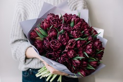 Very nice young woman holding huge beautiful blossoming mono bouquet of fresh purple tulip flowers on the grey background