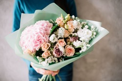 very nice young woman in a blue sweater holding a beautiful blossoming flower bouquet of fresh hydrangea, roses, carnations, matthiola, in pink and pastel cream colors on the grey wall background