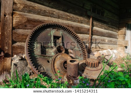 Very old and rusty huge rural metal device mechanical parts lying near the barn and illuminated by evening sun #1415214311