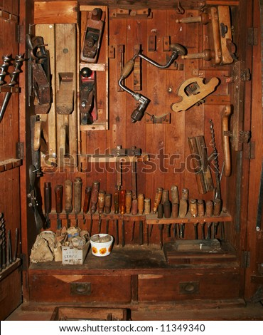 Very old and worn woodworking tools in worn down cabinet