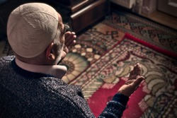 Very old bearded Muslim man at his 80's with a prayer cap praying to Allah at his home on his prayer in Ramadan month