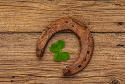 Very old cast iron metal horse horseshoe, fresh clover leaf. Good luck symbol, St.Patrick's Day concept. Antique wooden background, horse accessories