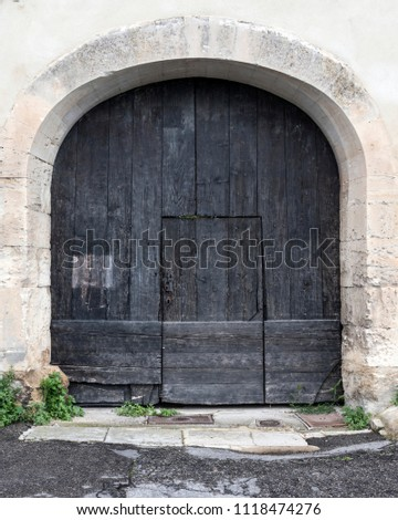 very old dark wooden arched door in ancient limestone wall of house in french provence #1118474276