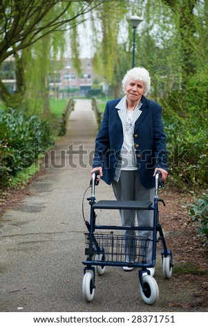 Very old lady with blue walker walking outdoor