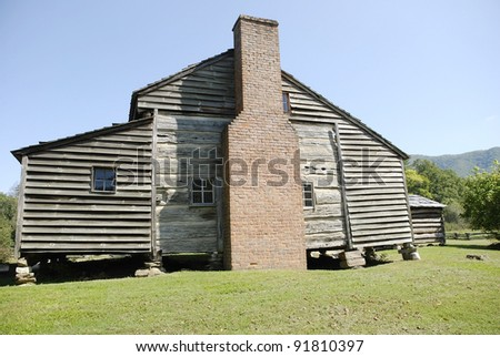 Very old log house has additions with rough plank siding for Log and brick home
