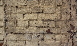 Very old painted Brick wall with peeling beige paint. Vintage Wall With Peeled Plaster. Retro Grunge Wall. Brick Wall With White Uneven Stucco