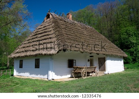Very old polish white hut with thatched roof
