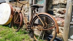 very old rusty bicycle stands against the wall of an old building.