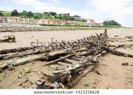 Very old shipwrecked boat on the coast of Zumaya, Spain, visible when the sea level descends.