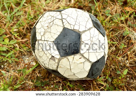 Very old soccer ball on the ground, vintage tone