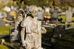 Very old stone angel (>150 years old) on a gravestone in a cemetery