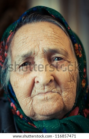 Very old woman alone in a scarf.