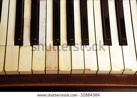 very old wooden piano with ivory keys broken and scratched