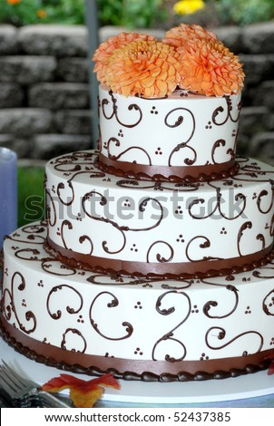 Very Ornate Brown and white wedding cake with marigolds on top.