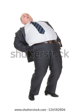 Very overweight man in a stylish suit and tie with acute back ache bending over backwards to alleviate the pain with an agonised expression on his face isolated on white