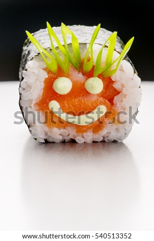 Very positive little roll in close up. Pictured with mayo smiling face on a salmon and bunch onion as a hair on a sushi. Funny shot of a food.
