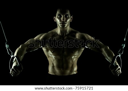 very power athletic guy ,  execute exercise on  on sport-apparatus, in  sport-hall, on black background, isolated