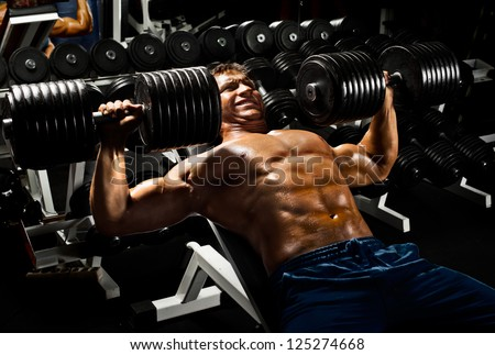 very power athletic guy ,  execute exercise press with  dumbbells, in sport hall