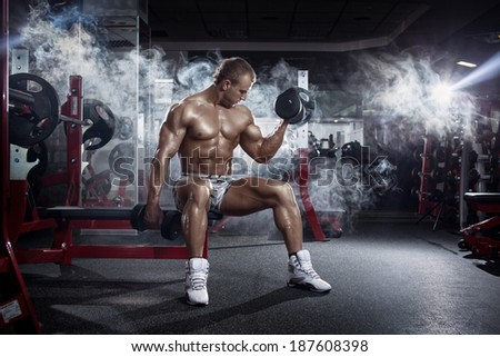 very power athletic guy execute exercise press with dumbbells workout in the gym