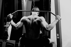 very power athletic guy , execute exercise tightening on horizontal bar, in sport-hall,