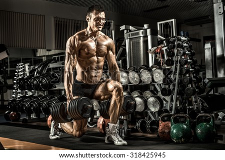 very power athletic guy ,  execute exercise with  dumbbells, in gym