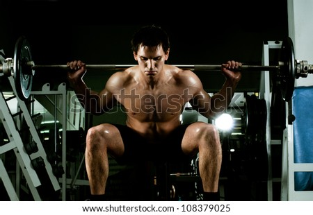 very power athletic guy ,  execute exercise with  dumbbells, in  sport-hall
