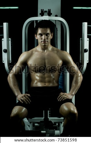 very power athletic guy ,  sit on  on sport-apparatus, in  sport-hall, beauty glamour light