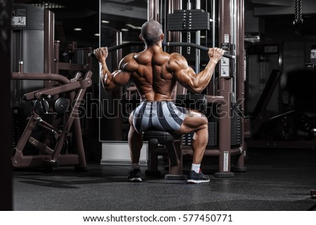 very power athletic guy training back workout in the gym. #577450771
