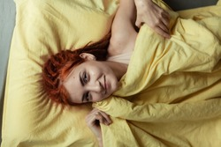 Very pretty redhead girl with dreads on bed in bedroom in the morning. A feminine, gentle girl. Healthcare and Sleep Concept.