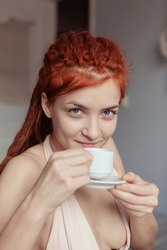 Very pretty redhead girl with dreads on bed in bedroom in the morning. A feminine, gentle girl. Coffee morning concept.