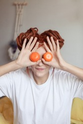 Very pretty redhead girl with dreads on bed in bedroom in the morning. A woman juggling with mandarins and fooling around