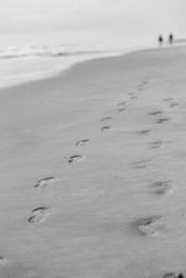 Very quiet, moody shoreline scene of two sets of footprints in the sand by the sea mark the path of two beach walkers in the distance moving away from the camera, 2021