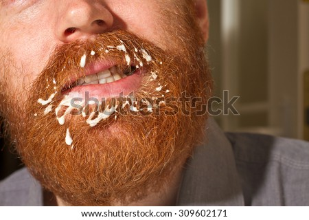Very red beard male with a filth on the mustache and the beard in white color, could be a cream or milk or yogurt