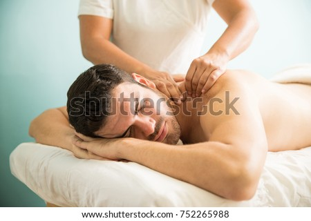 Very relaxed young Latin man getting a deep tissue massage on his back in a wellness and spa clinic