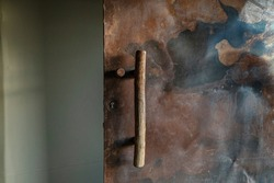 Very rough and rusty metal door has a rustic long wooden pull handle.