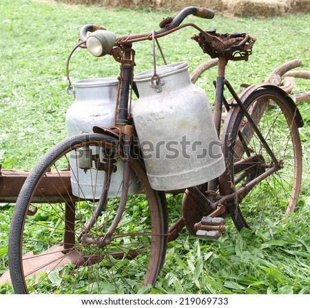 very rusty old bike of the milkman with two alluminium milk cans and broken saddle