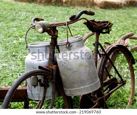 very rusty old bike of the milkman with two old milk cans and broken saddle