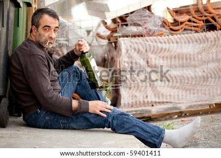 very sad man drinking wine on sidewalk near trashcan
