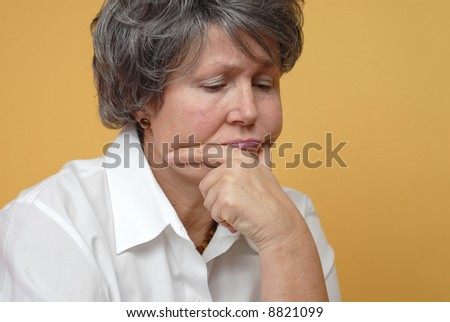 Very sad older woman in thought on yellow background