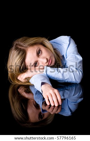 very sad, unhappy and worried woman in blue plain shirt, studio shoot isolated on black background