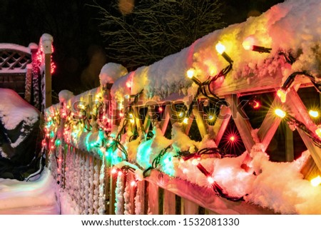 Very shiny Christmas decorations outside at night in Northern countries, Led lamps usage to save energy for green environment, slightly blurred lamps with long light beams hung on wooden fence. Sweden